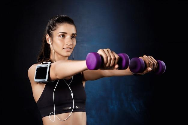 Молодая красивая спортивная девушка тренировки с гантелями над темной стеной. Бесплатные Фотографии