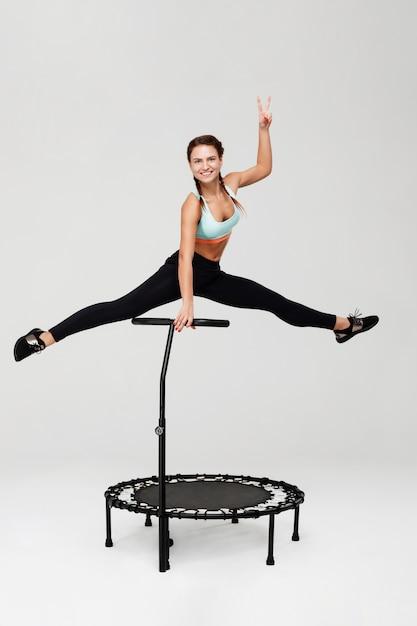 Женщина делает сплит, прыжки вверх, показывая знак мира, весело улыбаясь Бесплатные Фотографии