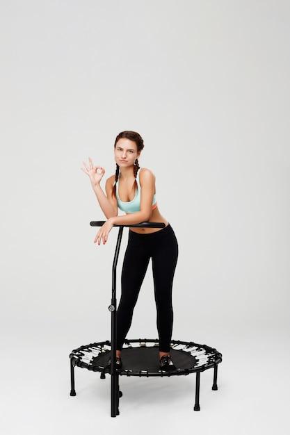 Славная женщина в одежде спорта показывая одобренный знак смотря прямо Бесплатные Фотографии