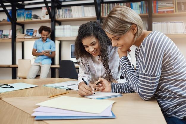 一緒に宿題をして、プレゼンテーションのエッセイを書いて、良い気分で試験の準備をするペアの美しい若い多民族学生の女の子のクローズアップ 無料写真