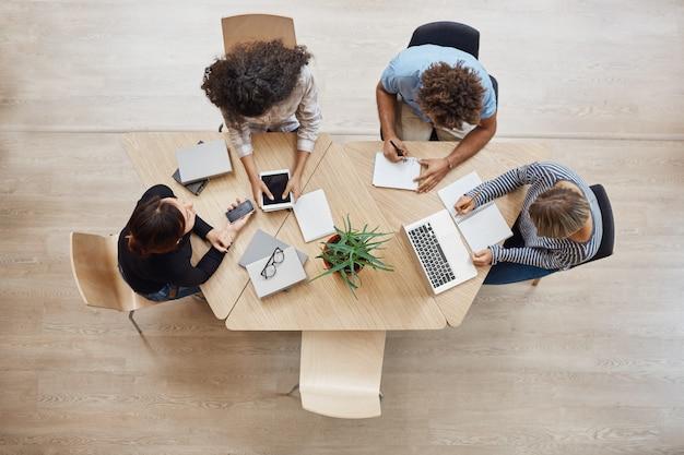 上からの眺め。ビジネス、スタートアップ、チームワークの概念。スタートアップパートナーがコワーキングスペースに座って、将来のプロジェクトについて話し、ラップトップとデジタルタブレットでの作業の例を調べます。 無料写真