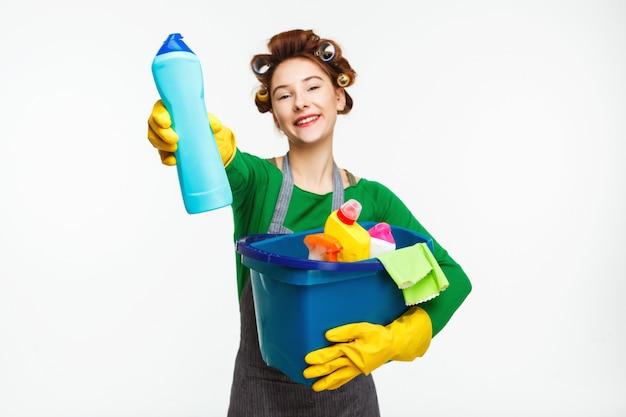 Красивая домохозяйка держит чистящие средства и показывает бутылку Бесплатные Фотографии