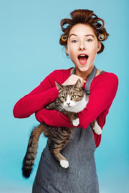 Очаровательная девушка с широкой улыбкой с кошкой в руках позирует Бесплатные Фотографии