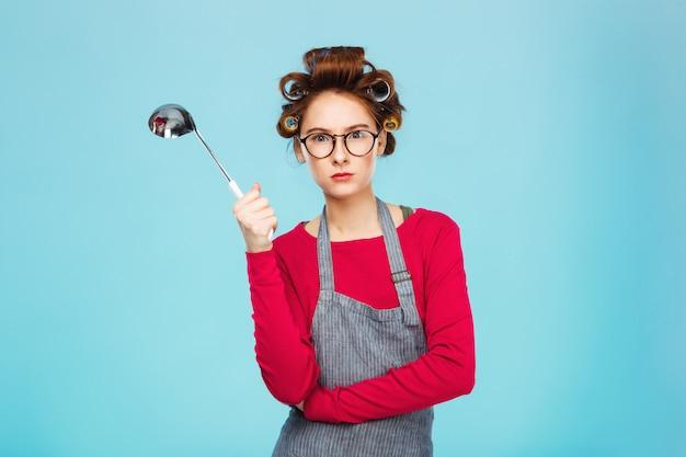 素敵な面白い女の子が危険な鍋と水色の壁の上に立ってから非表示にします 無料写真