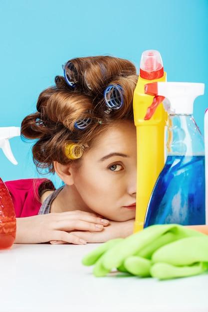 素敵な魅力的な女性がボトルとクリーニングツールの後ろに隠れます 無料写真