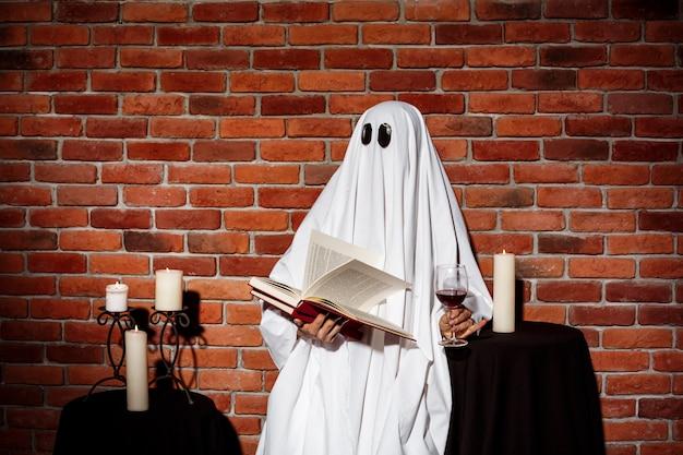 ゴーストの本とレンガの壁の上のワインを保持しています。ハロウィーンパーティー。 無料写真