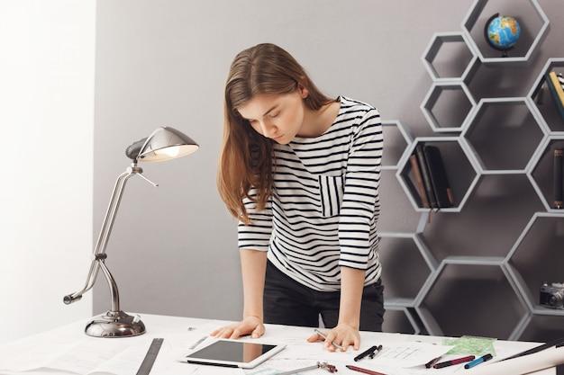 テーブルの近くに立って、デジタルタブレットで見て、いくつかの詳細を理解しようとするスタイリッシュなカジュアルな服装で黒い髪の若い格好良い深刻な女性デザイナー学生。 無料写真