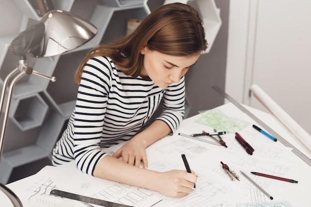 非公式の縞模様の服を着て、快適なコワーキングスペースのテーブルに座って、多くの文房具を使用して彼女の仕事をしている若いヨーロッパのフリーランスエンジニアのトリミングビュー。 無料写真