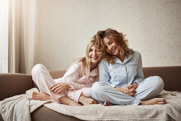 Кто может понять лучше, чем мама. две красивые девушки сидят на диване в пижаме, обнимаются, выражают нежные чувства и привязанность, являются близкими друзьями, сплетничают и разговаривают небрежно Бесплатные Фотографии