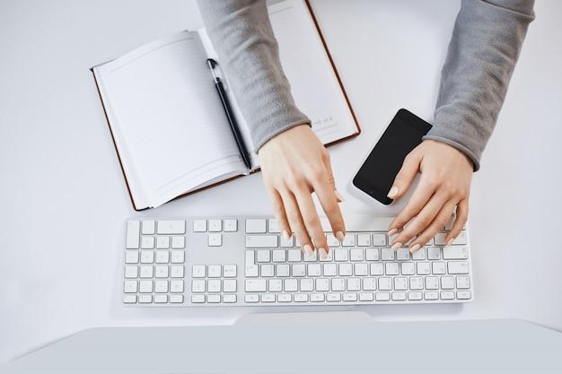 キーボードで入力してコンピューターとガジェットを操作する女性の手のトリミングされた肖像画。現代の女性フリーランサーが会社の新しいプロジェクトを設計し、ノートとスマートフォンでメモをとる 無料写真