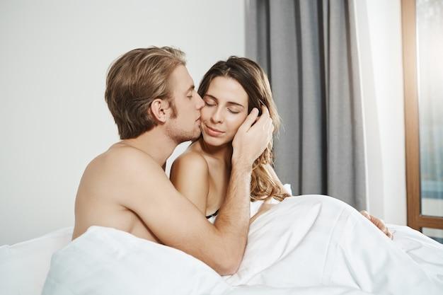 昼間一緒にベッドに横たわっている間、頬に魅力的な妻を優しくキスするハンサムな夫の肖像画。寝室に寄り添うカップル、周りをすべて忘れてしまったカップル 無料写真