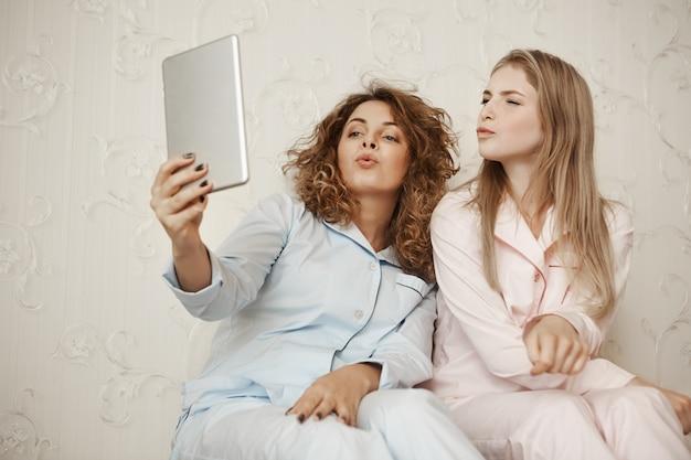 Две красивые подружки сидят дома в пижамах, веселятся, принимая селфи с цифровым планшетом, складывая губы, словно отправляя воздушный поцелуй, выражая дружелюбие и счастье Бесплатные Фотографии