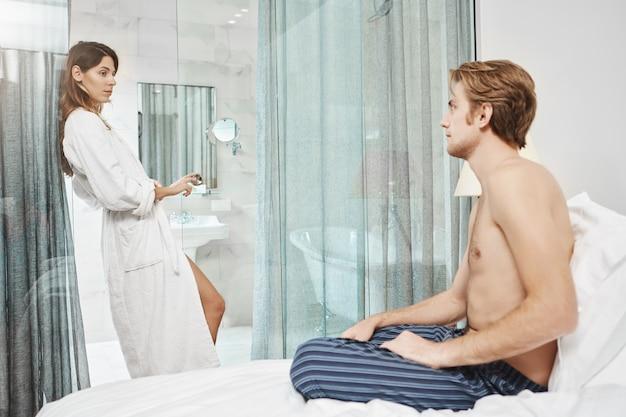 ホテルのバスローブが戸口に立って、情熱的な表情でベッドに座っている彼女のボーイフレンドを見て魅力的なヨーロッパの女性の肖像画。休暇中に愛のカップルがめったに彼らの寝室を離れる 無料写真