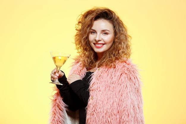 Крупным планом портрет веселой улыбающейся красивой брюнетки кудрявой девушки в розовой шубе держит бокал для коктейля над желтой стеной Бесплатные Фотографии