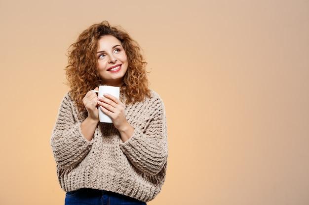 Крупным планом портрет веселой улыбающейся красивой брюнетки кудрявой девушки в вязаном свитере держит чашку над бежевой стеной Бесплатные Фотографии
