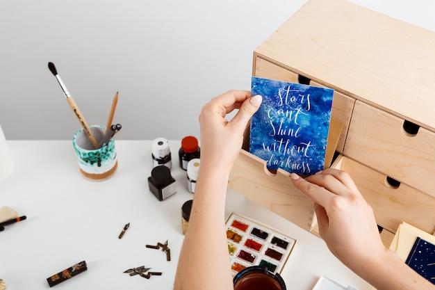 Девушка рука держит открытку со словами звезды не могут светить без тьмы. Бесплатные Фотографии