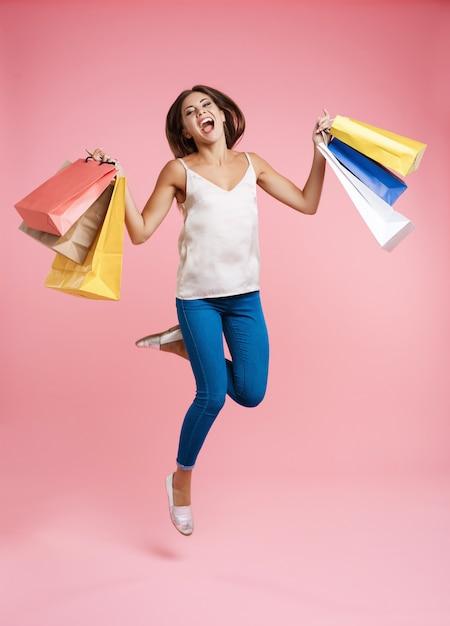 Счастливая женщина покупок прыгает с кучей сумок Бесплатные Фотографии