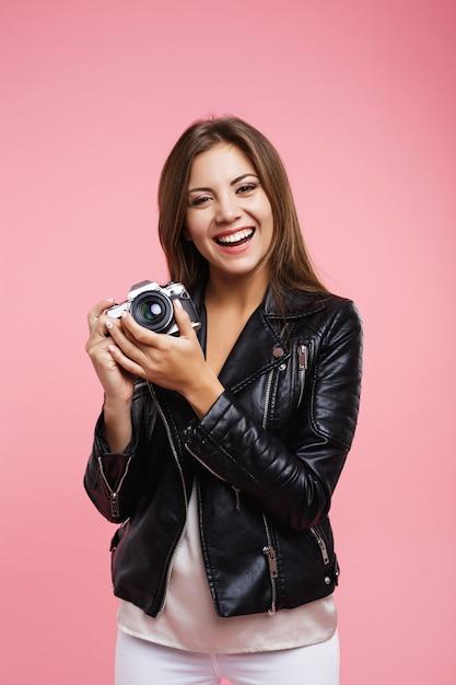 Улыбающаяся хипстерская женщина в повседневной одежде держит старую камеру Бесплатные Фотографии