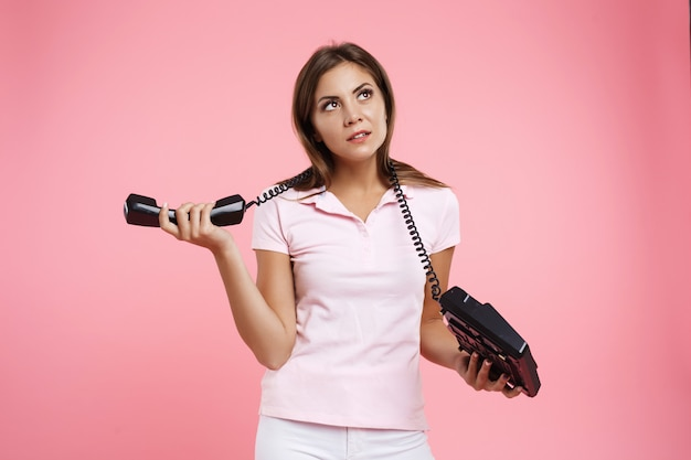 Красивая молодая женщина, держащая стационарный телефонный шнур вокруг шеи Бесплатные Фотографии