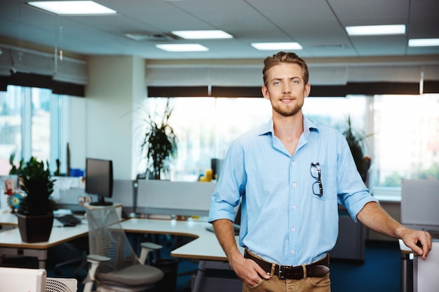 若いハンサムな成功した実業家笑顔、ポーズ、オフィス 無料写真