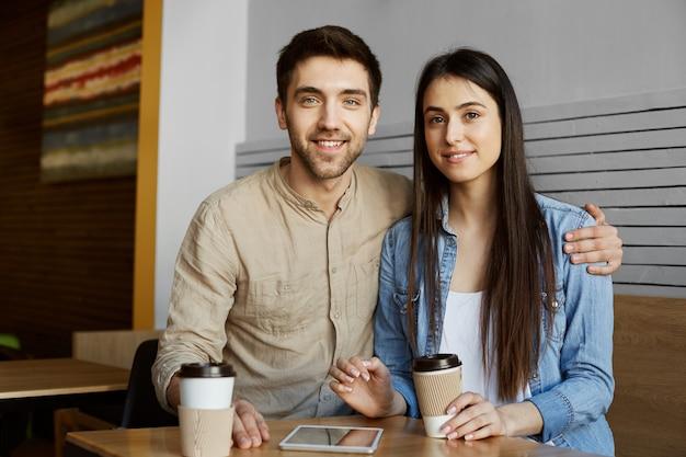 カジュアルな服を着た黒髪の美しい若いペアは笑顔でコーヒーを飲み、視点のスタートアッププロジェクトに関する大学の記事で写真のポーズをとっています。 無料写真