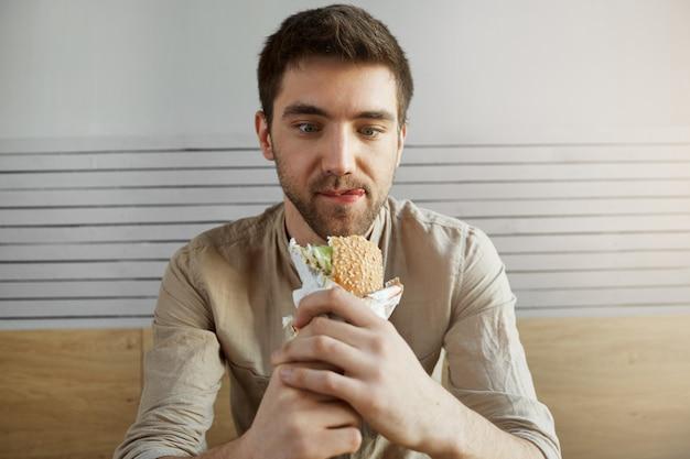 魅力的な黒髪の男がカフェに座って、サンドイッチで幸せそうな表情で見て、仕事で一日中何かを食べて幸せです。ハンバーガーを食べに行く空腹の男。 無料写真
