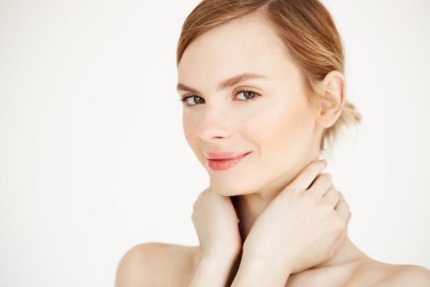 首に触れて笑ってきれいな健康な肌を持つ美しい柔らかい女の子。フェイシャルトリートメント。 無料写真