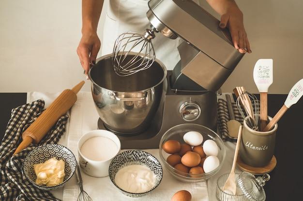 Кондитер девушка готовит торт Premium Фотографии