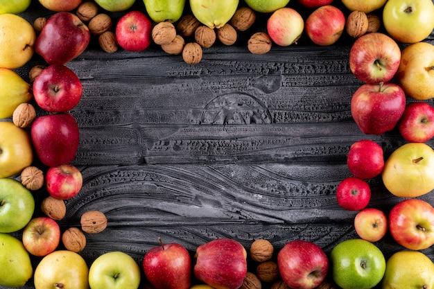 Вид сверху яблоки и груши с орехами и грецкими орехами с копией пространства на серой деревянной горизонтали Бесплатные Фотографии