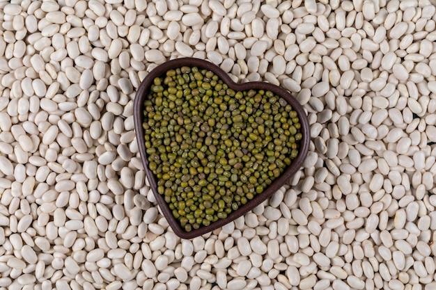 白豆とハート型のボウルにエンドウ豆のトップビュー 無料写真