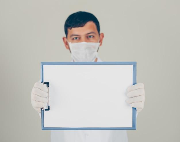 Доктор взгляда со стороны при перчатки смотря и держа держатель бумаги. горизонтальный Бесплатные Фотографии