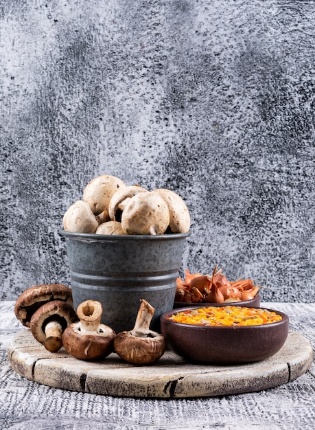 レンズ豆、ボウルに小さな玉ねぎ、ボウルとバケツに茶色と白のキノコのセット 無料写真