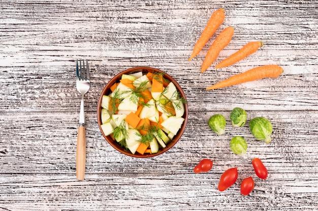 フォークニンジン大根チェリートマトキャベツとセラミックボウルの野菜サラダ 無料写真