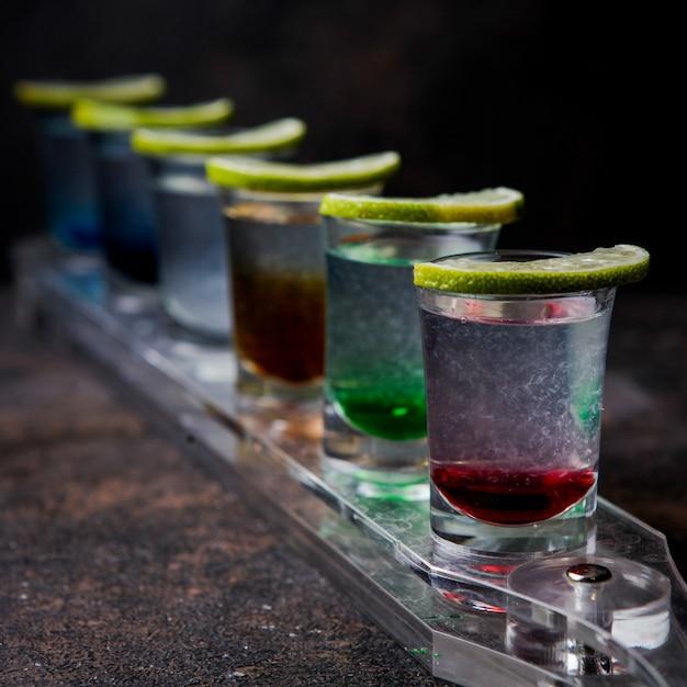 Крупным планом рюмки с цветными напитками и лаймом на стекле Бесплатные Фотографии