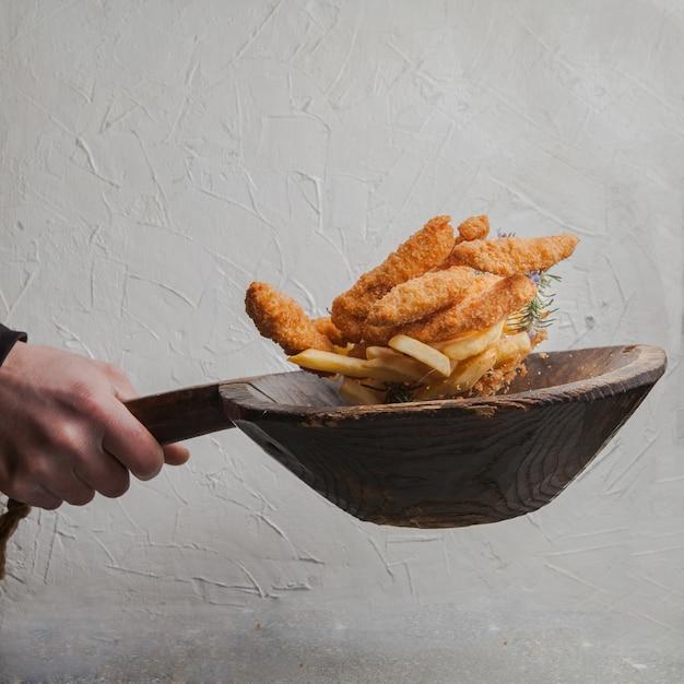 Куриные наггетсы с картофелем фри и человеческая рука в мухе Бесплатные Фотографии