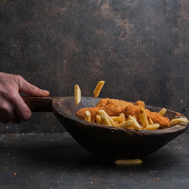 Куриные наггетсы с картофелем фри и человеческой рукой в деревянной тарелке Бесплатные Фотографии