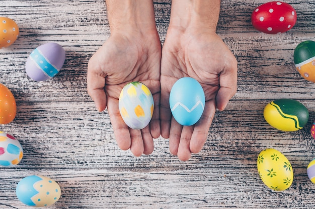Пасхальные яйца в руках человека на деревянных фоне. Бесплатные Фотографии