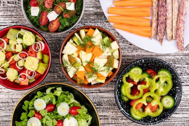 白い木製の表面のピーマン豆人参タマネギレタストップビューに異なるボウルに異なる野菜サラダ 無料写真