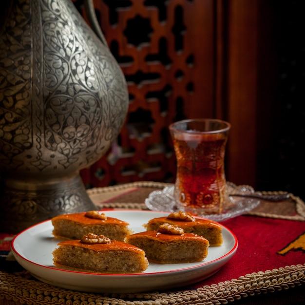 Вид сбоку пахлава с бокалом чая и железный старинный чайник в белой тарелке Бесплатные Фотографии