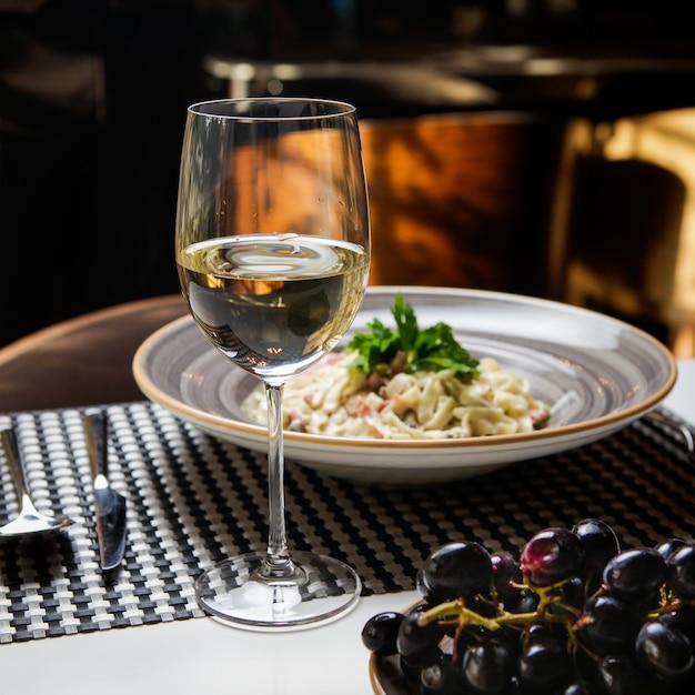 Бокал вина с макаронами и виноградом в круглой тарелке Бесплатные Фотографии