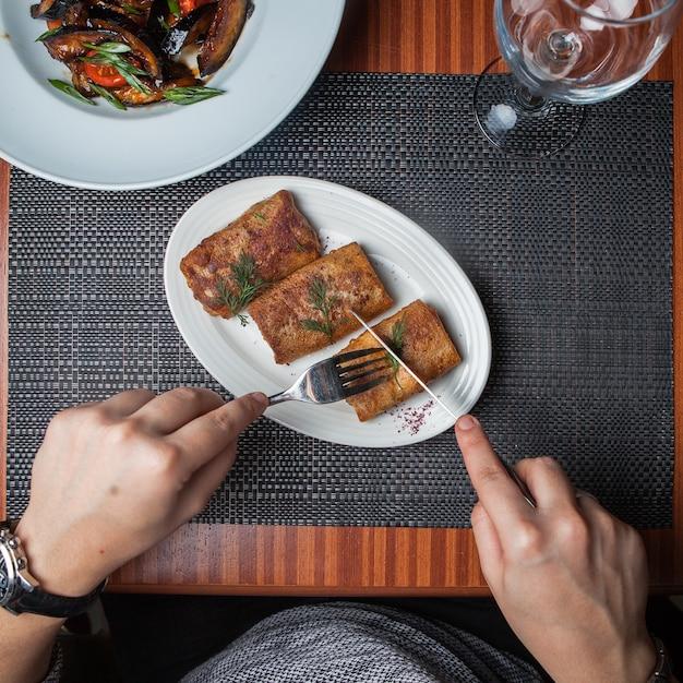 ナイフとフォークで肉とサイドビューのパンケーキと揚げナスと木製のテーブルの上の白い皿に人間の手 無料写真