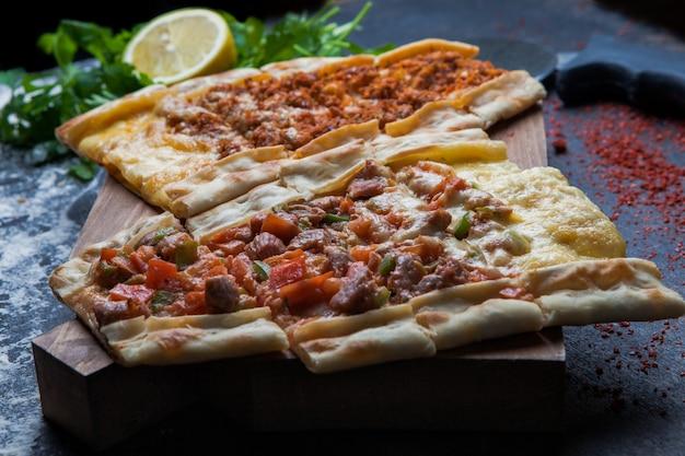 Боковой вид с кусочками мяса и петрушки, лимона и ножа для пиццы в разделочной доске Бесплатные Фотографии