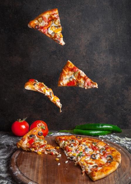 コショウとトマトのピザのサイドビューピザと調理器具のピザのスライス 無料写真