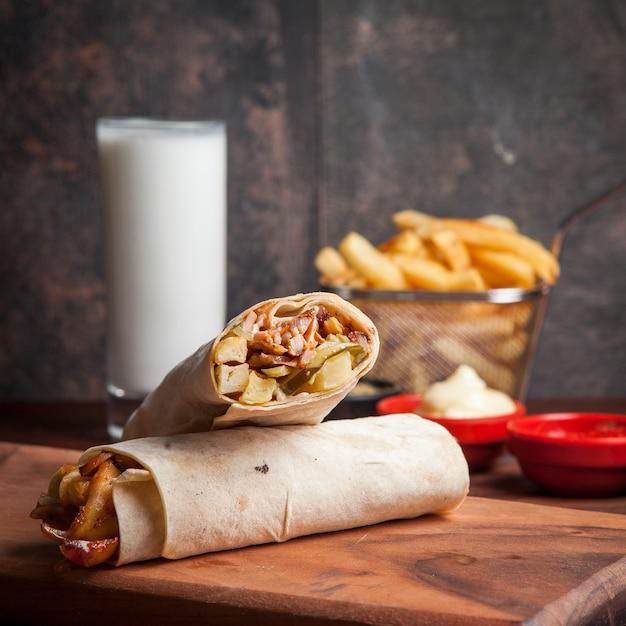 Вид сбоку шаурмы с жареным картофелем и айраном и майонезом в посуде Бесплатные Фотографии