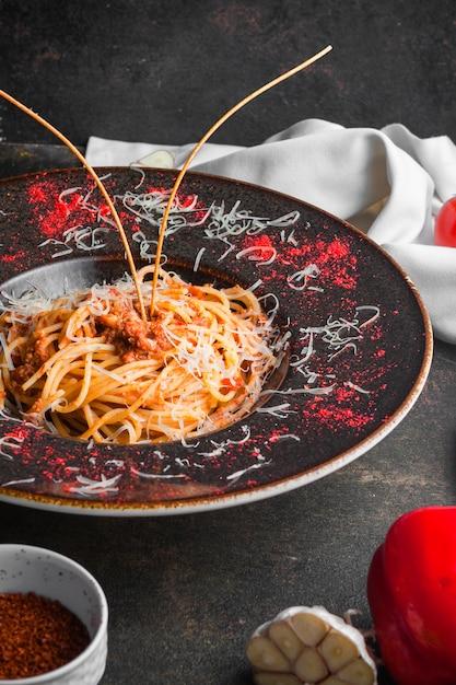 Вид сбоку спагетти с мясным фаршем и чесноком в круглой тарелке Бесплатные Фотографии