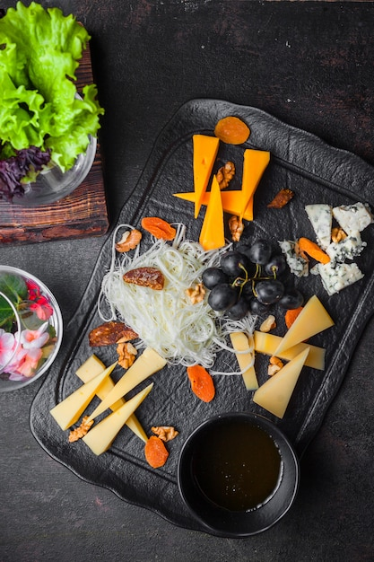 Вид сверху сырное ассорти с виноградом и орехами и медом в лотке Бесплатные Фотографии