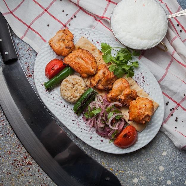 トップビューチキンケバブと野菜の炒め、玉ねぎのみじん切りとアイランと白い皿にナイフ 無料写真