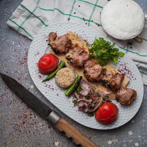 揚げ野菜と玉ねぎのみじん切りとアイランと白い皿にナイフと上面図ラムケバブ 無料写真