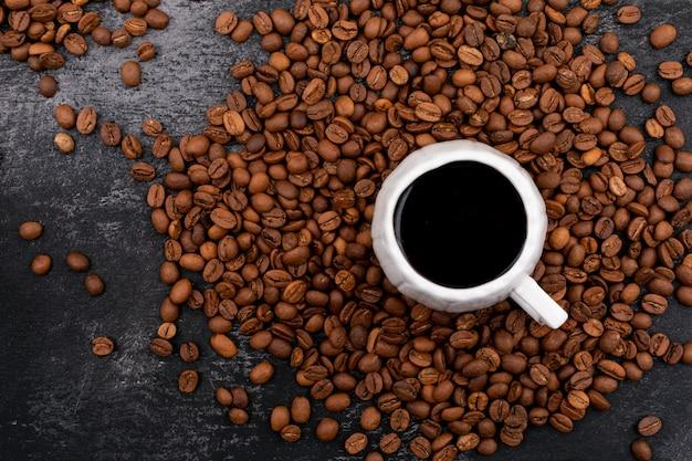 Чашка кофе в окружении кофейных зерен на черной поверхности Бесплатные Фотографии