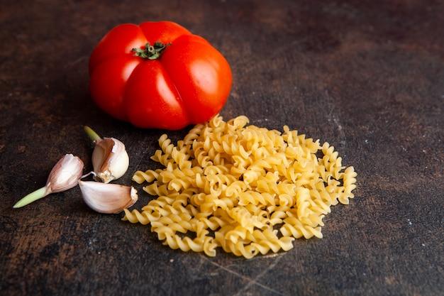 Макарон взгляда высокого угла с томатом и чесноком на темной текстурированной предпосылке. горизонтальный Бесплатные Фотографии